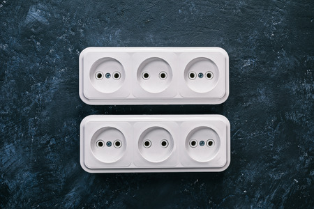 sockets: White triple electric sockets on the spotty black surface
