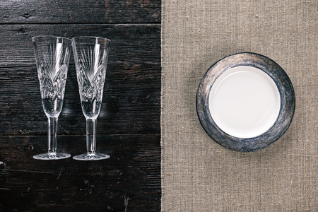 two and a half: Still life with two empty wineglasses and plate on the half covered table. Flat lay Stock Photo