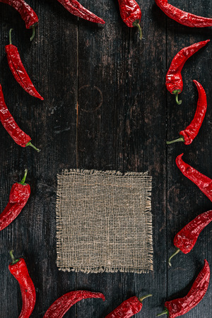 pimento: Border of dried red chili peppers on dark wood with burlap napkin