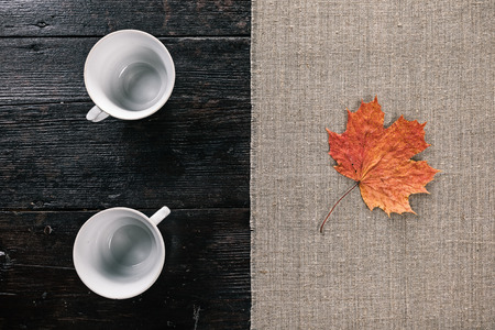 two and a half: Still life with two empty tea cups and fallen maple leaf on the half covered table. Flat lay Stock Photo