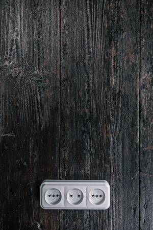 grounded plug: White triple electric socket on the dark wooden surface Stock Photo