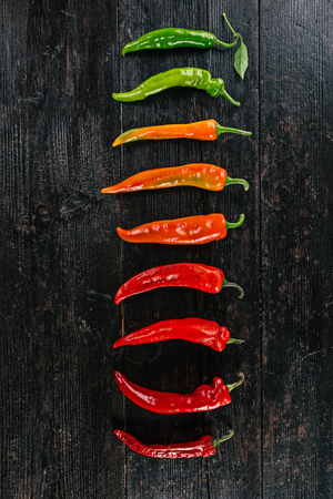 pimento: Row of hot peppers gradually changing their color from green to dark red