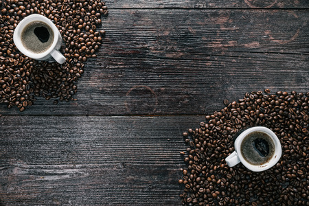 awaking: White ceramic cups of coffee on the table covered with coffee beans. Flat lay