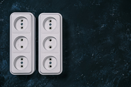 grounded plug: White triple electric sockets on the spotty black surface