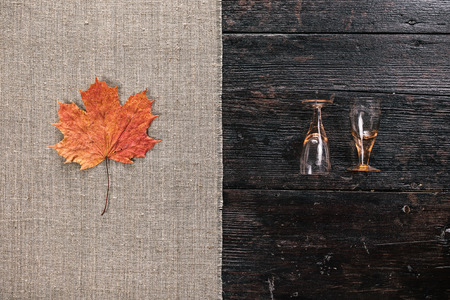 two and a half: Still life with two empty wineglasses and fallen maple leaf on the half covered table. Flat lay Stock Photo