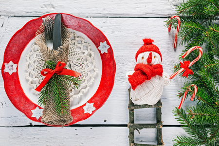 christmas toy: Christmas border of evergreen twigs with toy snowman on the ladder near the plate. Overhead view Stock Photo