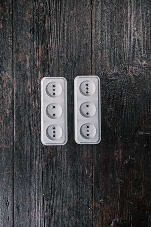 sockets: White triple electric sockets on the dark wooden surface