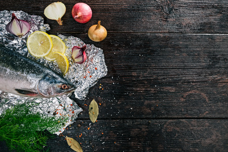 potherb: Fresh whole salmon fish on foil sheet with veggies and spices. Flat lay
