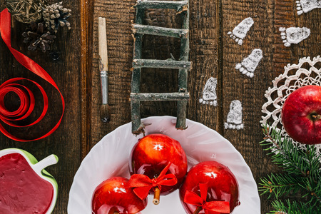 dwarf christmas: Little white powder footprints and tools of elf, dwarf or brownie on the christmas table with candy apples Stock Photo