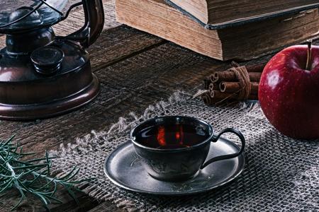 tea lamp: Slill-life with tea cup, books, kerosene lamp, red apple and cinnamon sticks