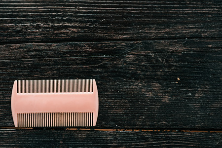 body grooming: Used doubleside hair comb on the dark browm wood