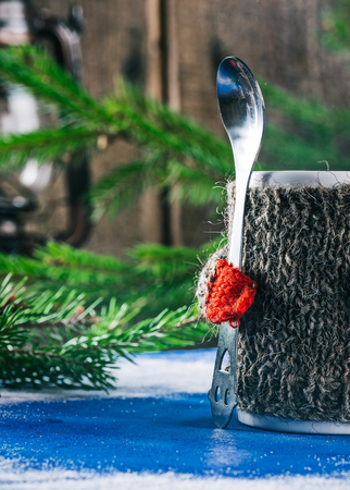 warmer: Mug with woolen warmer holding teaspoon on the table with christmas decorations Stock Photo