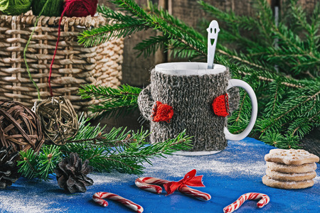 warmer: Mug with woolen warmer on the table with candy canes, cookies and christmas decorations