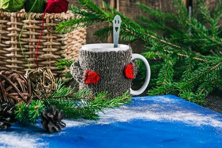 warmer: Mug with woolen warmer on the table with yarn balls and christmas decorations
