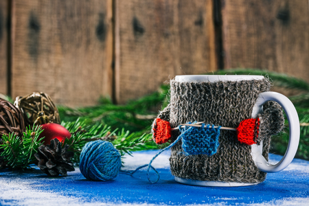 warmer: Mug with woolen warmer holding toothpicks as knitting needles on the table with christmas decorations Stock Photo