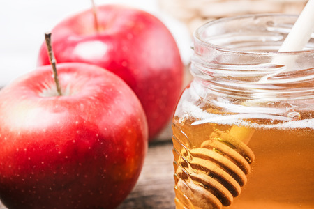 gold cans: Closeup of red apples and glass can of honey on the wooden surface.