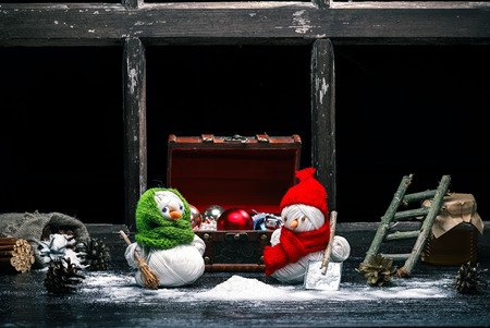 brooming: Handmade toy snowman and snowgirl of yarn skeins brooming and shoveling the snow over black background. Color toning