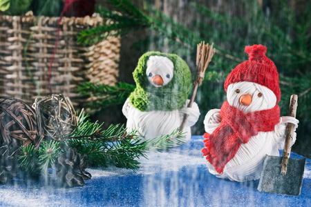 personages: Handmade yarn snowmen holding shovel and broom on the background of christmas decorations