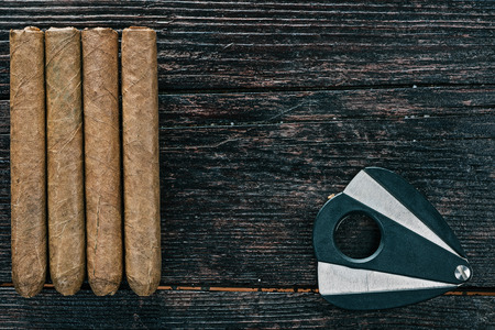 leaf cutter: Group of cigars and cigar cutter on the dark brown wooden surface. Flat lay. Selective focus Stock Photo