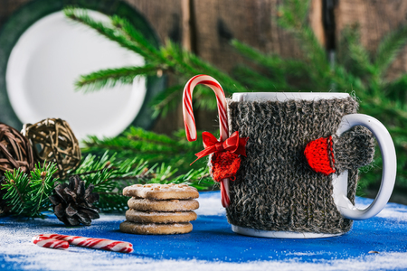 warmer: Mug with woolen warmer holding candy cane on the table with christmas decorations