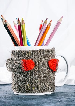 warmer: Mug in wool warmer full of color pencils