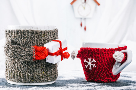warmer: Big mom mug in wool warmer giving the gift box to little kid cup