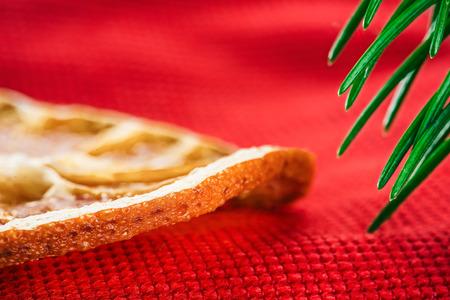 evergreen branch: Dried orange slice on red textured fabric under evergreen branch. Macro detail view