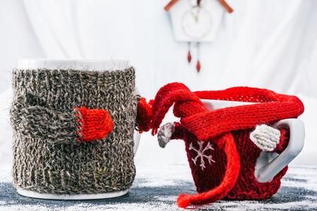 warmer: Big mom mug in wool warmer helping little kid cup to tie the scarf