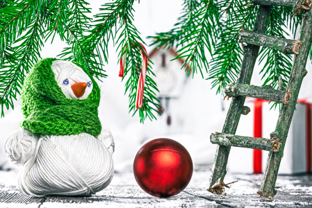 christmas tree ball: Handmade yarn snowman with red christmas ball near toy twig ladder under evergreen branches