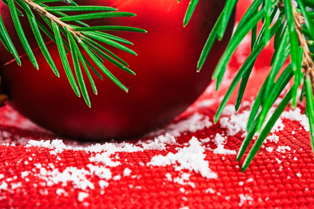 evergreen branch: Red christmas ball on textured red fabric covered with snowflakes under evergreen branch. Macro detail view