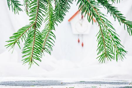 reloj cucu: Handmade toy cuckoo clock on the white wall through evergreen branches. Concept of christmas advent. Selective focus Foto de archivo