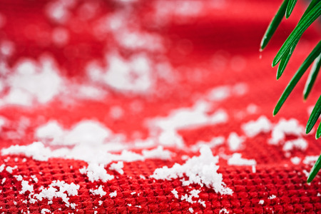 evergreen branch: Red textured fabric covered with snowflakes under evergreen branch. Macro detail view