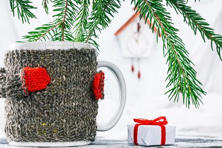 warmer: Big mug in wool warmer near the gift box under evergreen branches Stock Photo
