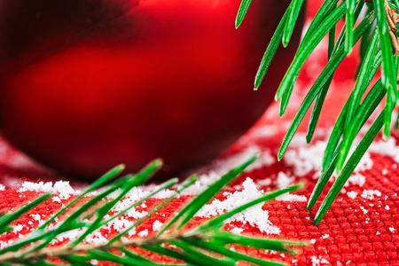 evergreen branch: navidad bola roja en tela roja con textura cubierto con copos de nieve bajo rama perenne. Ver detalles de la macro