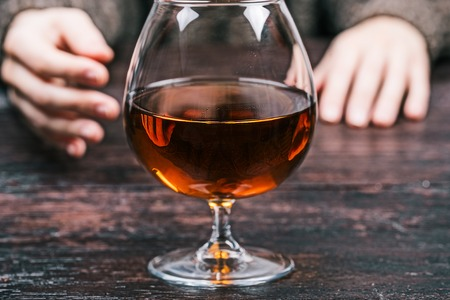 big behind: Human hands behind big glass of brandy. Front closeup view