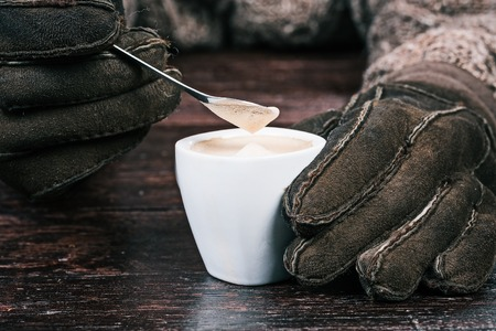 sheep skin: Human hands in winter sheep skin gloves holding cup of coffee and teaspoon. Front closeup view