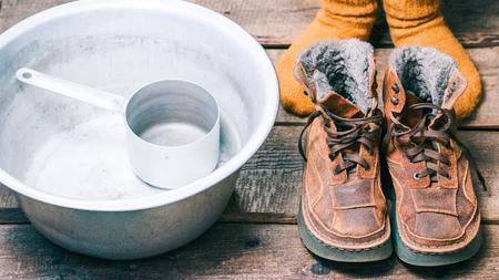 hosiery: Feet wearing wool socks near winter fur boots and basin on the floor before footbath. Color toning Stock Photo