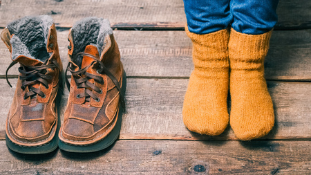 hosiery: Feet wearing wool socks next to winter fur boots on the wooden floor. Color toning
