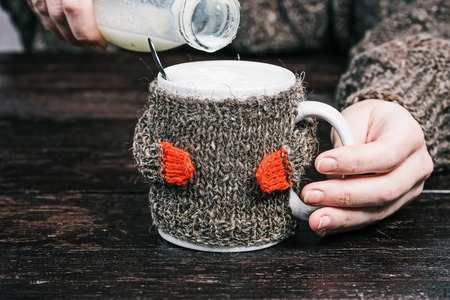 warmer: Human hands holding mug of milk in wool warmer. Front view