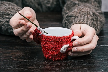 warmer: Human hands holding little cup in wool warmer with unfinished sleeve. Front view