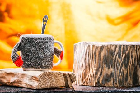teaspoon: Teacup wearing wool sweater on wood stand. Smiling teaspoon inside