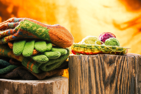 knitwear: Unfinished knitting and colorful yarn next to knitwear stack over fire background Stock Photo