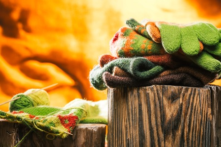 knitwear: Knitwear stack on wood stamp and unfinished needlework over fire background Stock Photo
