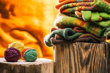 knitwear: Colorful knitwear stack and yarn balls on wood stamps over fire background