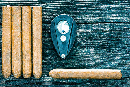 leaf cutter: Group of cigars and cigar cutter on the dark brown wooden surface. Flat lay. Color toning Stock Photo