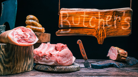 cutting tools: Various pieces of pork meat on butchers counter. Butchers chopping and cutting tools. Wooden sign hanging above them