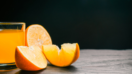 sparkling water: Sliced orange and glass of orange sparkling water on dark background