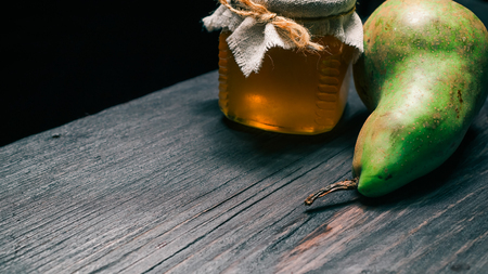 Pear next to tied can of honey on black wood. Selective focus