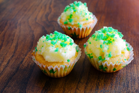 butter icing: Cupcake muffin butter cream icing green wooden baskground homemade three