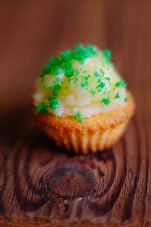 butter icing: Cupcake muffin butter cream icing green wooden baskground homemade closeup